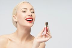 Beautiful woman applying lip gloss Royalty Free Stock Image