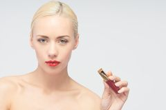 Beautiful woman applying lip gloss Stock Photos