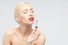 Beautiful woman applying lip gloss Stock Image