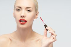 Beautiful woman applying lip gloss Royalty Free Stock Photos
