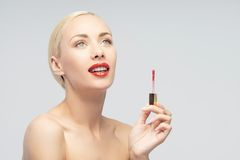 Beautiful woman applying lip gloss Royalty Free Stock Images