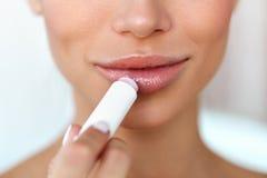 Beautiful Woman Applying Lip Protector On Lips Skin. Beauty. Lips Skin Care. Beautiful Woman Face With Full Lips Applying Hygienic Lip Balm, Lipcare Stick stock images
