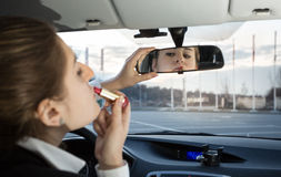 Beautiful woman applying lipstick in car Royalty Free Stock Images