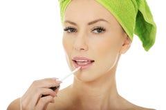 Beautiful woman applying lipstick. Royalty Free Stock Images