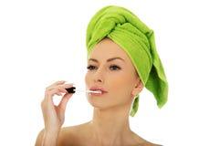 Beautiful woman applying lipstick. Royalty Free Stock Photography