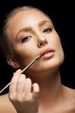 Beautiful woman applying lipstick Stock Image