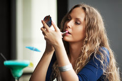Beautiful woman applying a lipstick Stock Image