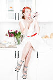 Beautiful woman applying lipstick on the kitchen Stock Image