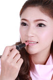Beautiful woman applying lipstick Royalty Free Stock Image