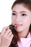 Beautiful woman applying lipstick Royalty Free Stock Image