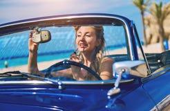 Beautiful woman applying lipstick in a retro car. Beautiful woman applying lipstick in a retro cabriolet car near the sea Stock Image