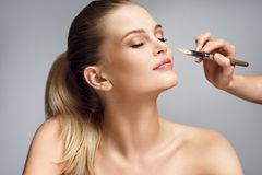 Beautiful woman applying liquid foundation on her face. On grey background Royalty Free Stock Photography