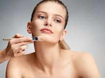 Beautiful woman applying liquid foundation on her face. On grey background Stock Images