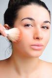 Beautiful woman applying make-up Stock Images