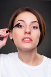 Beautiful woman applying make up Stock Photography