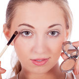 Beautiful woman applying make up on face Royalty Free Stock Images