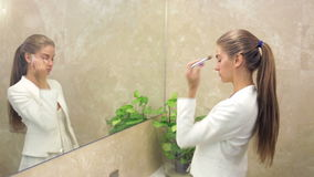 Beautiful woman applying make up stock video