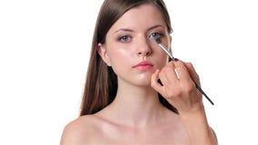 Beautiful woman applying make up on white background Royalty Free Stock Photos