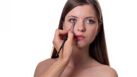 Beautiful woman applying make up on white background Stock Photos