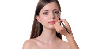 Beautiful woman applying make up on white background Stock Photography