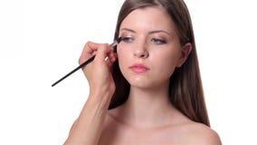 Beautiful woman applying make up on white background Royalty Free Stock Photo