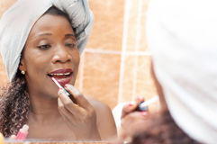 Beautiful woman applying makeup in the bathroom. Stock Photography