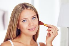 Beautiful woman applying makeup with a big brush royalty free stock photo