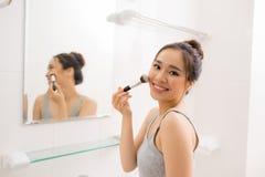 Beautiful woman applying makeup blusher in her bathroom Royalty Free Stock Photo