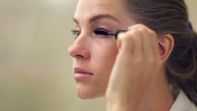Beautiful woman applying makeup on eyelid with brush stock video