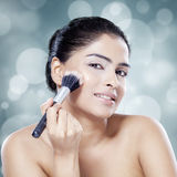 Beautiful woman applying makeup on face Stock Photography