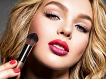 Beautiful woman applying makeup. Glamour. Fashion stock photography