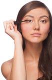 Beautiful woman applying mascara. On her eyelashes, isolated on white background Stock Photos