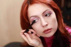 Beautiful woman applying mascara on eyelashes Stock Images