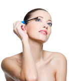 Beautiful woman applying mascara on eyelashes Royalty Free Stock Photography