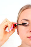 Beautiful woman applying mascara on her eyelashes Royalty Free Stock Images