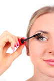Beautiful woman applying mascara on her eyelashes Stock Photo