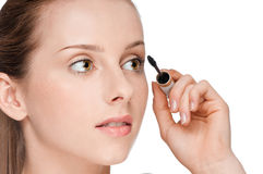 Beautiful woman applying mascara on her eyelashes Royalty Free Stock Photo