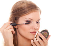 Beautiful woman applying mascara on her eyelashes Royalty Free Stock Image