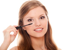 Beautiful woman applying mascara on her eyelashes Stock Images