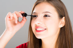Beautiful woman applying mascara on her eyelashes Royalty Free Stock Photography