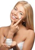 Beautiful woman applying moisturizer cream Stock Images