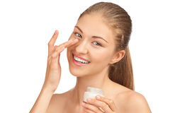 Beautiful woman applying moisturizer cream. Portrait of young beautiful woman applying moisturizer cream on her face, isolated on white background Stock Photos
