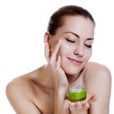 Beautiful woman applying moisturizer cream. Happy smiling beautiful woman applying moisturizer cream on the face Royalty Free Stock Images