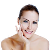 Beautiful woman applying moisturizer cream. Happy smiling beautiful woman applying moisturizer cream on the face Stock Image