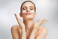 Beautiful woman applying moisturizing cream on her face. Photo of woman with flawless skin on grey background. Skin care and beauty concept Royalty Free Stock Photo