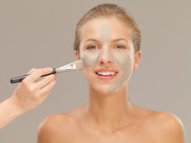 Beautiful woman applying mud mask with brush Royalty Free Stock Photo