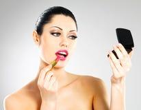 Beautiful woman applying pink lipstick on lips Stock Photo