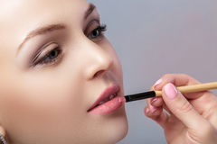 Beautiful woman applying pink lipstick using brush for makeup Royalty Free Stock Image