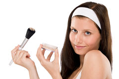 Beautiful woman applying powder with brush Stock Photo