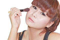 Beautiful woman applying powder on cheek with brush Stock Image